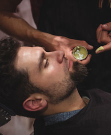 mid-section-of-barber-applying-cream-on-