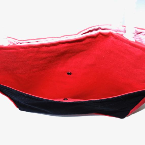 La tela que lleva el bordado principal hace también de bolsa exterior al frente, la cual se cierra con un botón tipo snap.