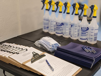 a black table fills with clipboards, papers, folders, masks and water bottle sprays