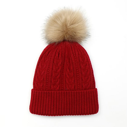 Deep red cable knit winter hat with natural faux fur pom pom