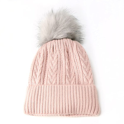 Pale pink cable knit hat with a light grey faux fur bobble