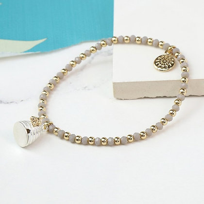 Grey bead bracelet with a silver and gold beehive charm