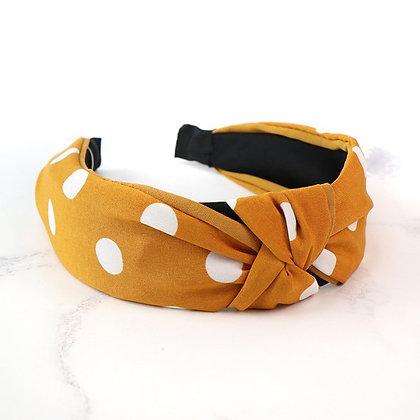 Mustard fabric covered headband with white polkadots