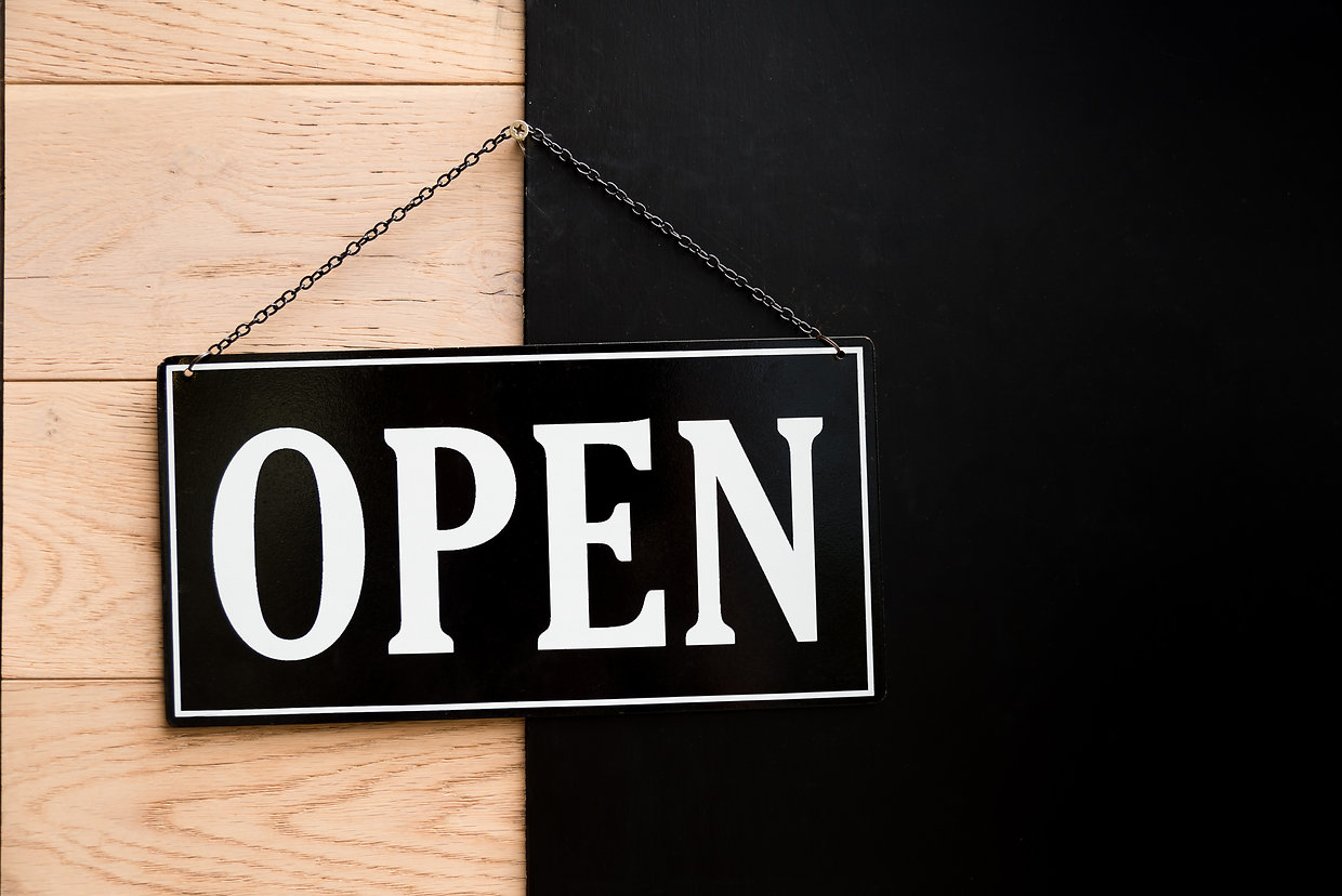 Open sign hanging on wooden wall in rest