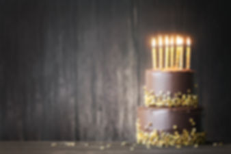 Chocolate birthday cake with gold candle