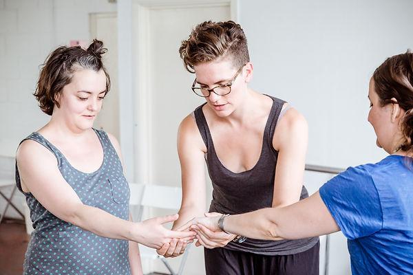 dance teacher guiding same sex couple