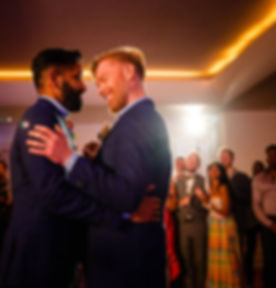 Two men dancing together on their wedding day. Smiling with friends and family around them