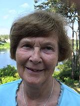 Margaret Tompsett outdoors near waterway wearing an aqua blouse