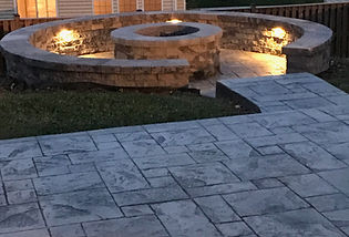 Stamped concrete patio with a seating wall and a firepit