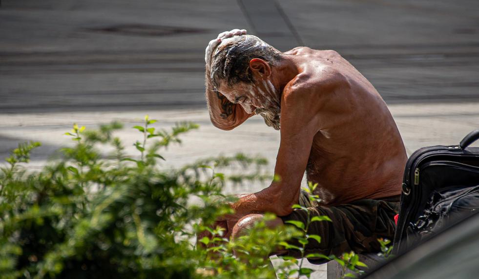 Slovakia, Bratislava. Homeless man washi