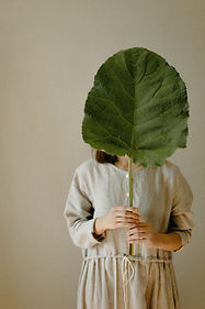 person-holding-a-big-leaf-covering-his-f