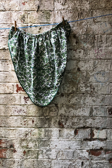 a green paisley vintage apron against a brick wall