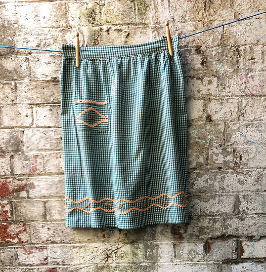 A green plaid pinny with mustard trim against brick wall