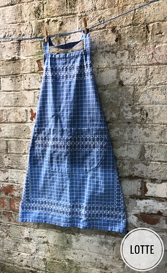 A blue vintage apron with white stitching against a brick wall