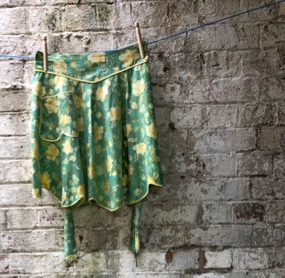 Beautiful yellow and green vintage apron against brick