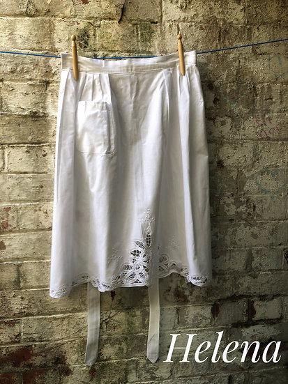 white vintage apron hanging against a  brick wall