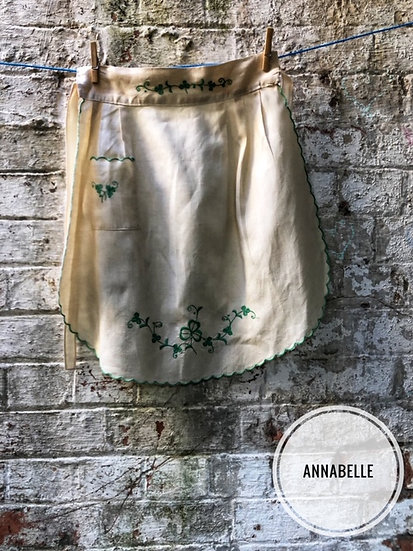 a cream vintage apron with green embroidery