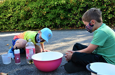 2 boys outside with science experiment.j