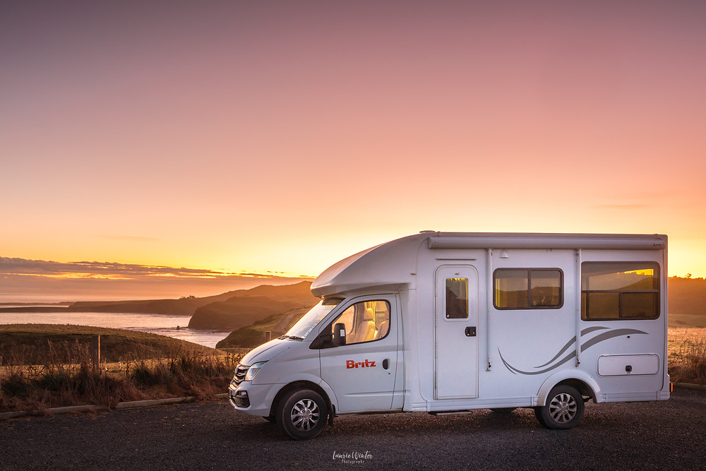 Britz Campervan parked at Slope Point under a pink sky