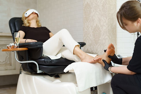 Specialist in beauty salon making pedicure and massage for female client. Relaxing at the