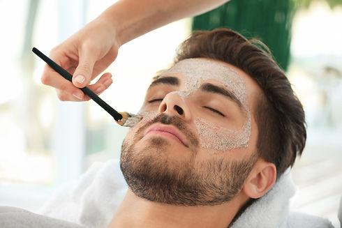 Beautician applying scrub onto young man's face in spa salon.jpg
