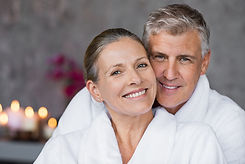 Portrait of mature married couple embracing with bathrobe and looking at camera. Happy sen
