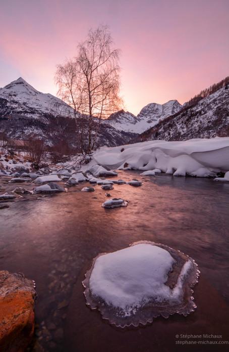 Aurore rose d'hiver, torrent et pierre glacée.