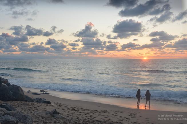 Promeneuses à la plage au coucher de soleil sur la côte Basque