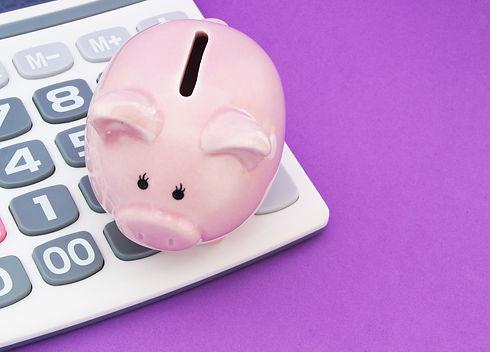 Piggy bank and calculator on purple back