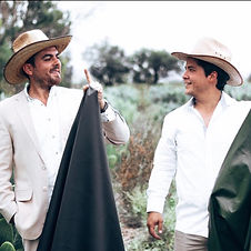 Two men in hats and formal looking cloths outside.