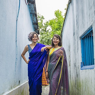 Two women in sarees posed between two buildings.