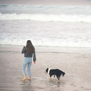 A woman in MUD jeans at the beach with a black and white dog.