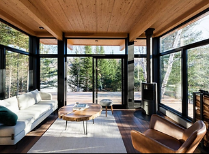 A liviing room with glass windows and trees outside the windows.