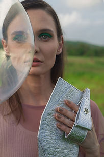 A woman holding a fish leather purse with a bubble in front of half her face.