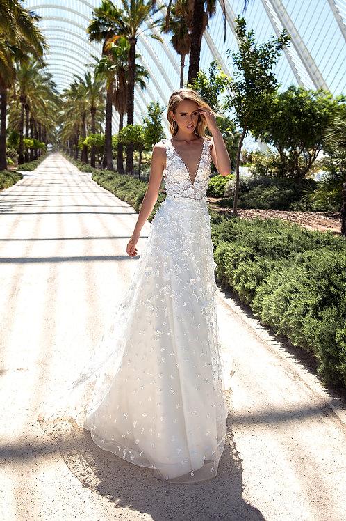 Mary Bella Elanna 3D-s virágokkal díszített esküvői ruhájában sétál egy szőke hajú lány