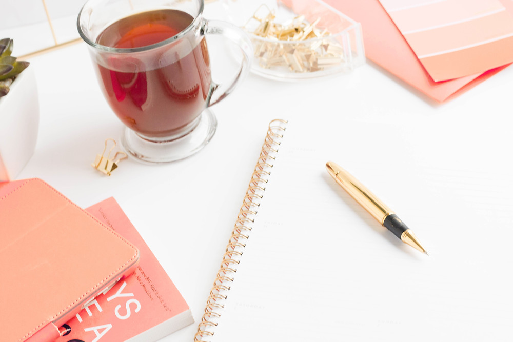 Flat lay photo with white notebook, color color books, clear glass mug of tea, gold pen, gold paper binder clips, on a white desk. Shanell Tyus, African American blogger, creative coach for aspiring creatives.