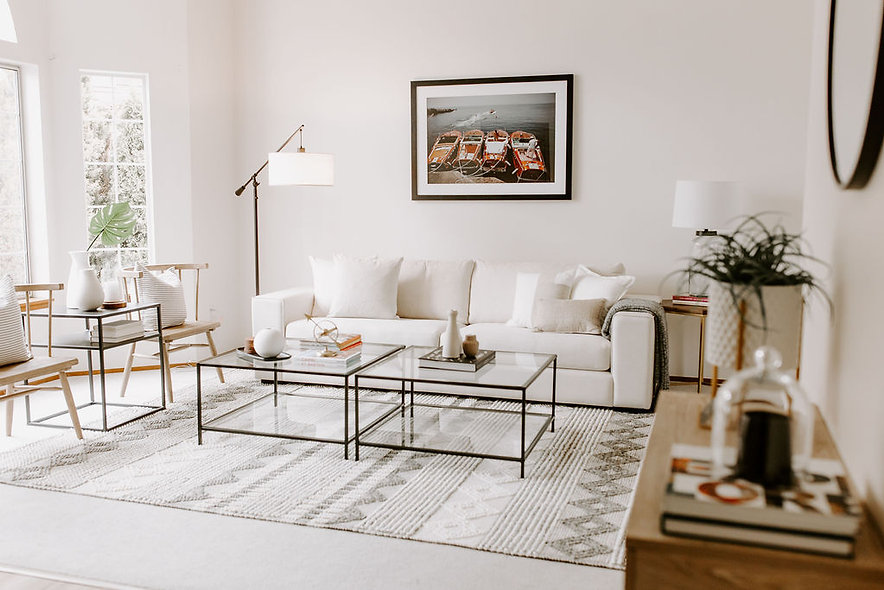 White couch in modern living room styling with glass coffee tables and boho chairs