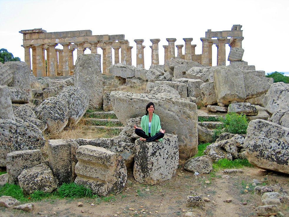 """Cynthia Daddona, the Modern Day Goddess®, meditates at the ancient Greek Temple """"E"""" in Selinunte, Sicily, Italy.  Southern Italy during ancient Greece was known as Magna Graecia, or Greater Greece."""