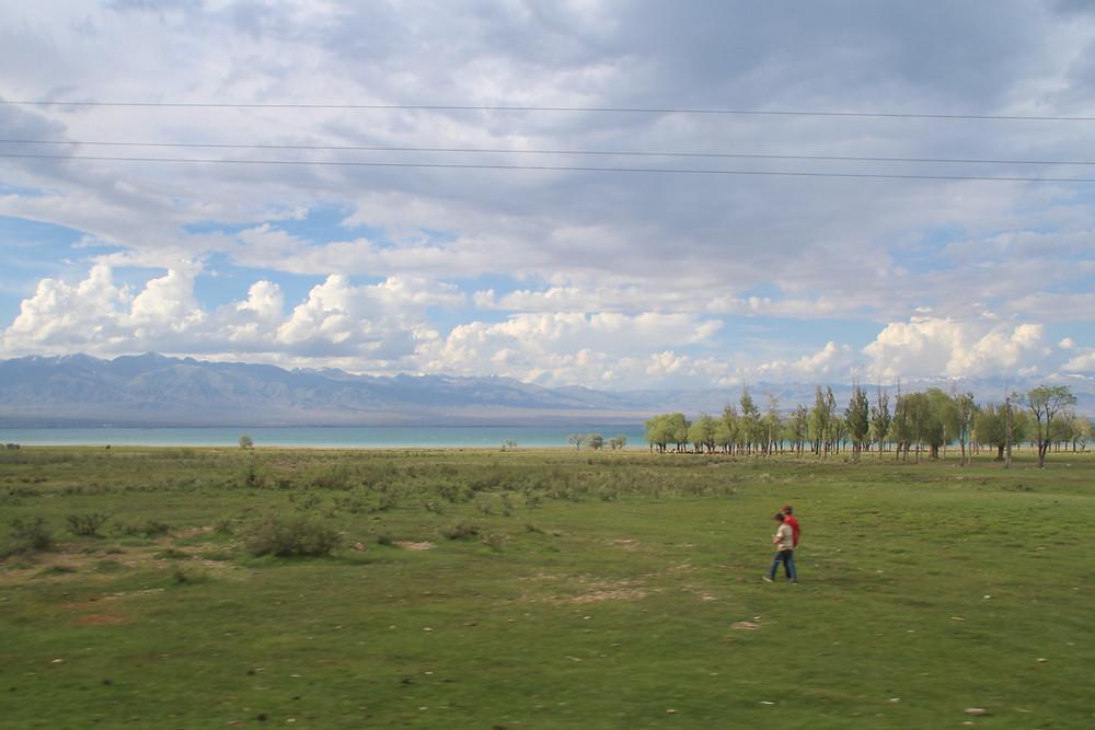 שני ילדים הולכים על משטח עשב, ברקע אגם איסיק קול