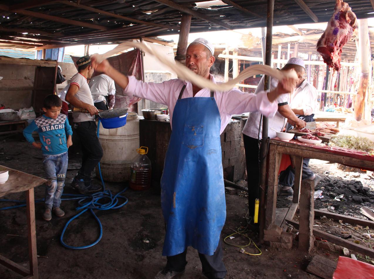 איש אויגורי מכין את הלגמן - האטריות המקומיות המפורסמות