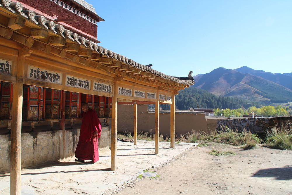 נזיר טיבטי מסובב את גלגלי הקורה בשיאחה, סין