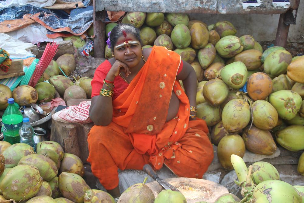 מוכרת אגוזי קוקוס הודית, יושבת בין הסחורה שלה
