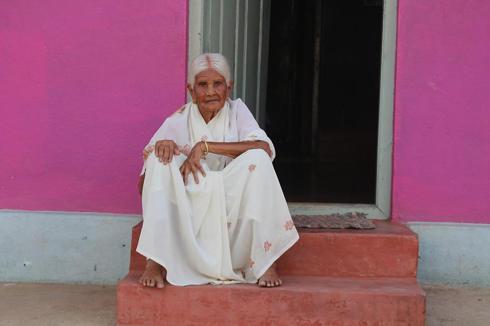 הודית מבוגרת עם שיער לבן, בלבוש לבן, יושבת בפתח בית