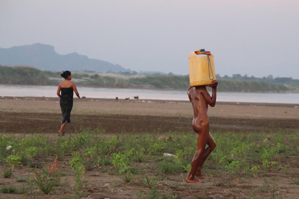 ילד סוחב ג'ריקן מים, ליד הנהר בפה-אן