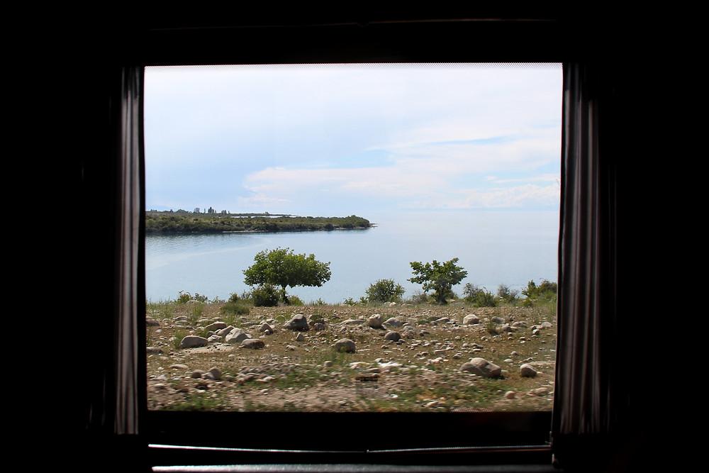נוף אגם איסיק קול בקירגיזסטן מבעד למסגרת חלון