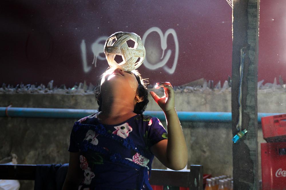 ילדה משחקת עם כדור הצ'ינלון במיאנמר