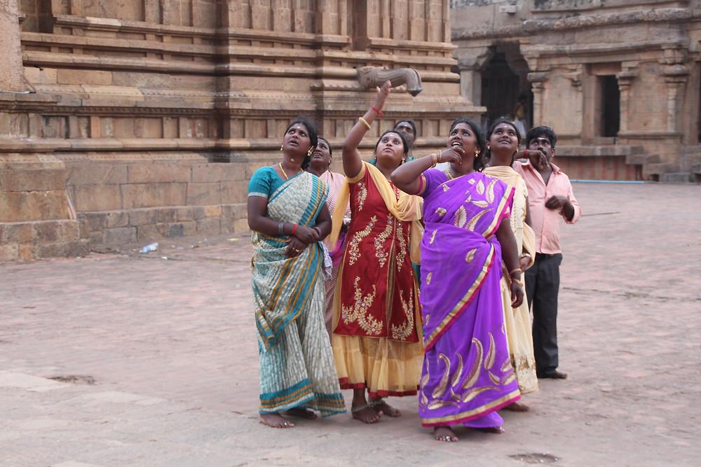 חבורת נשים הודיות מביטות למעלה במקדש