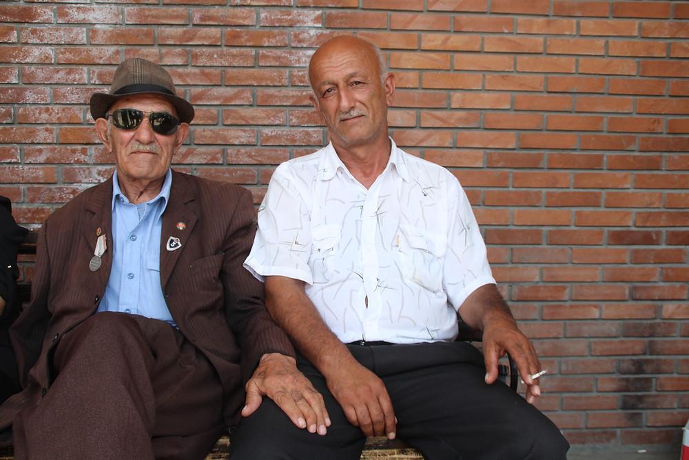 שני גברים אזרים יושבים אחד לצד השני