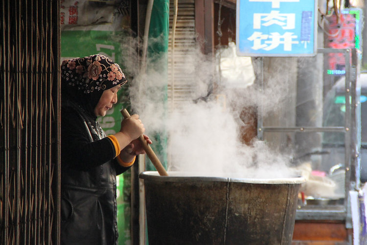 a woman cooking in Xi'an's streets