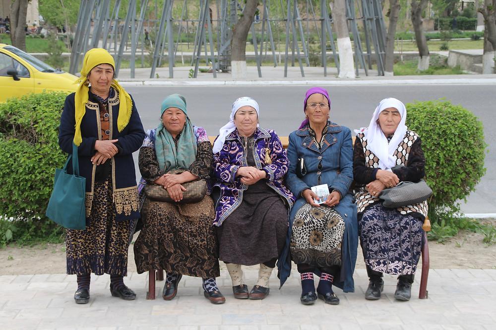 חבורת נשים אוזבקיות בביגוד מסורתי יושבות על ספסל